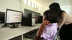 BURIRAM, THAILAND, SEPTEMBER 2013: A Thai teacher helps a young female Asian student in the computer lab at school in Buriram, Thailand.