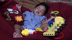 A cute little Asian toddler enjoys taking a nap in Bangkok, Thailand.