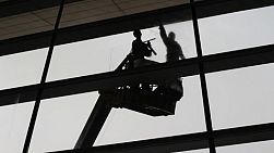 Two Asian window washers washing windows at an airport in China at lightning speed.