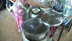 A Thai woman cooks Thai noodles for customers in a market in Chantaburi, Thailand.