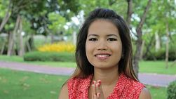 "A beautiful Thai girl does a traditional Thai ""wai"" greeting in the park in Bangkok, Thailand."