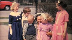 A bunch of well dressed kids get hugs and kisses from their favorite Aunt in the summer of 1962.
