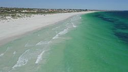 Drone shot flying above the clear water at Mullaloo Beach in Perth, Western Australia on a clear windy day.