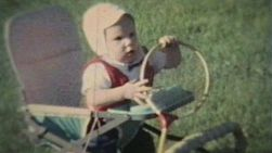 A cute baby boy plays outside and chews on a badminton racket in the back yard.