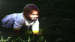 Baby girl attempting to crawl on grass in a yard, in September 1983.