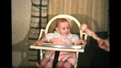 A cute red headed baby girl sits in her high chair and waits patiently for her dinner to arrive.