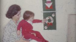 A cute baby girl gets distracted by a Christmas wall hanging in Trenton, New Jersey in 1958.
