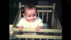 A cute red headed baby girl learns to stand in her crib and flashes a proud smile to the camera.