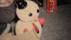 A grandfather harasses a cute baby girl at Christmas with a weird looking Frosty the Snowman doll.