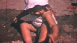 A cute little baby girl wearing a white bonnet playing at the beach on a sunny summer day in 1969. (Vintage 8mm film footage)