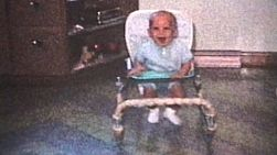 A cute little baby having a fun time running in his walker in the kitchen.