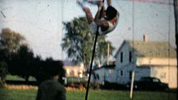 A dedicated young man practices his pole vaulting in his backyard in 1962.