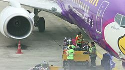 Baggage handlers loading luggage on a Nok Air plane at Don Muang Airport, Bangkok, Thailand.