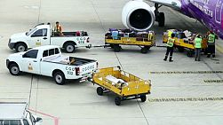 Baggage handlers offloading luggage from a plane at Don Muang Airport, Bangkok, Thailand.