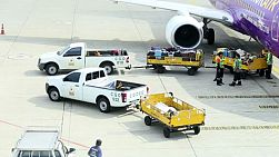 Baggage handlers ready to load luggage on a Nok Air plane at Don Muang Airport, Bangkok, Thailand.