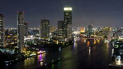 A time lapse of Bangkok at night, looking over the Chao Phraya river, with Saphan Taksin bridge and the sky train in view.