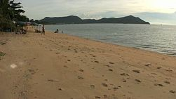 A tourist goes for a dip as the sun sets on a beautiful beach near Sattahip, Thailand.