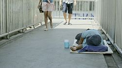 Beggar lying down on a footbridge, while people pass by ignoring the beggar.