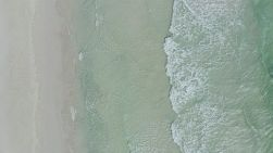 Bird's eye view of small waves onto a sandy beach on a windy day in Perth, Western Australia.