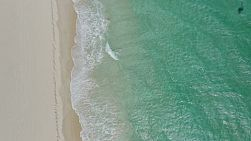 Bird's eye view of waves washing ashore on a windy day onto a beach in Perth, Western Australia.