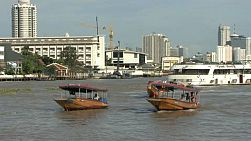 A classic shot of boats and traffic on the mighty Chao Phraya river in Bangkok, Thailand.