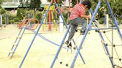Young boy climbing down a rope ladder in a playground.