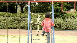 Young boy climbing up a rope ladder in a playground.