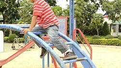 Young boy climbing on a climbing frame in a playground.