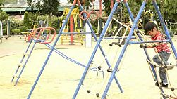 Young boy climbing on a rope ladder in a playground.