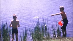 A couple of cute little blond haired boys spend time using a bucket to hunt fish in the lake during the summer of 1967.