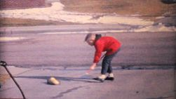 A cute boy enjoys playing with his toys in the driveway on a cool winter day in 1964.