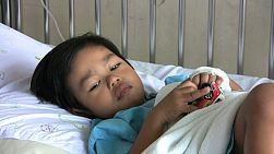 A sick little boy takes comfort in his toy cars while recovering from being ill in the hospital.