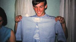 A handsome boyfriend checks out the new sweater that his lovely fiancee received at her bridal shower in 1967.