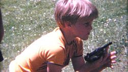 A group of little boys have fun blowing bubbles and shooting each other with their his toy guns in the summer of 1967.