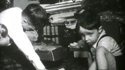 Two brothers enjoy playing with their new Christmas gifts in 1955 including their new airplane.