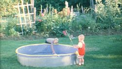 A couple of cute little blond haired boys spend time fishing in their back yard pool in the summer of 1967.