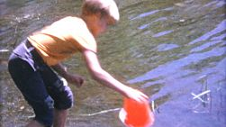 A group of cute little blond haired boys spend time using a bucket to hunt fish in the lake during the summer of 1967.