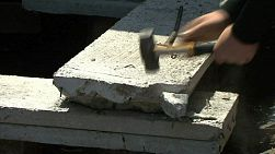 A man uses a hammer to smash off excess pieces of concrete off a cement slab.