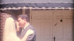 A beautiful bride gets a quick kiss from her older brother at her wedding in the summer of 1958.