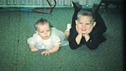 A little boy and his baby sister lay on the carpet in the living room and pose for the camera.