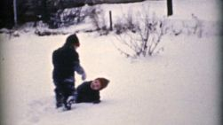Two cute little boys enjoy spending time fighting and playing in the snow in the winter of 1955.