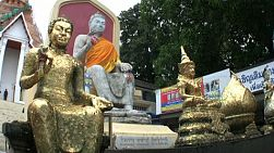 A tilt up shot of large gold plated Buddha statues in front of a Buddhist temple in Bangkok, Thailand.