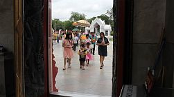 Families and friends enter the temple to begin the ceremony of a new novice becoming a monk in Bangkok, Thailand.