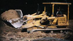 A bulldozer moves dirt on a job site prepping the ground for a new pool in 1967.