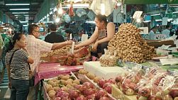 A happy couple buying some fruit at a fresh food market in Bangkok, Thailand.