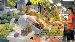 Man purchasing fruit at a fresh fruit market in Bangkok, Thailand, with a large variety of fruit for sale.