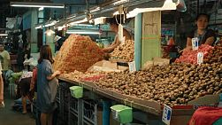 Customers buying mangosteen, rambutan and other fruits at a fresh fruit market in Bangkok, Thailand.