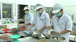 Technical university students learn the ropes at a canning factory.
