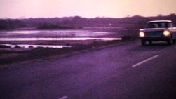 An old car cruises down the highway beside the ocean as the sun sets on this wonderful Venezuelan holiday in 1978.