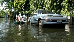 A Thai man checks out the condition of his car which is up on blocks above the flood waters in Bangkok, Thailand.